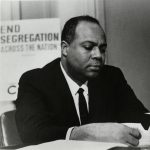 "Black and white photograph of James Farmer sitting in front of an ""End Segregation"" sign."