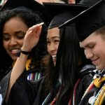 Image of three students in cap and gowns at Commencement